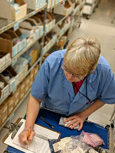 Worker Using Cycle Count Inventory Management in Manufacturing Facility